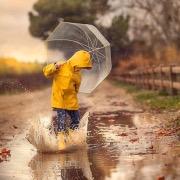 Мальчик прыгает по лужам